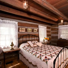 A cozy bed with antique covers in a log cabin room are is one of the accomodations at the Pioneer Trading Post